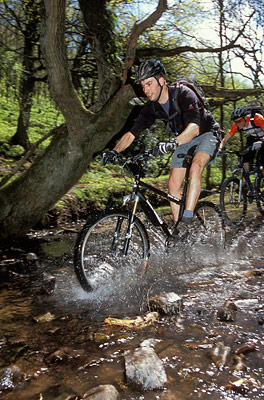 Mountain bike guide splashing through water